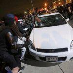 Manifestantes destruyen un vehículo en las afueras del edificio de la policía de Ferguson, en San Luis. foto edh / reuters.
