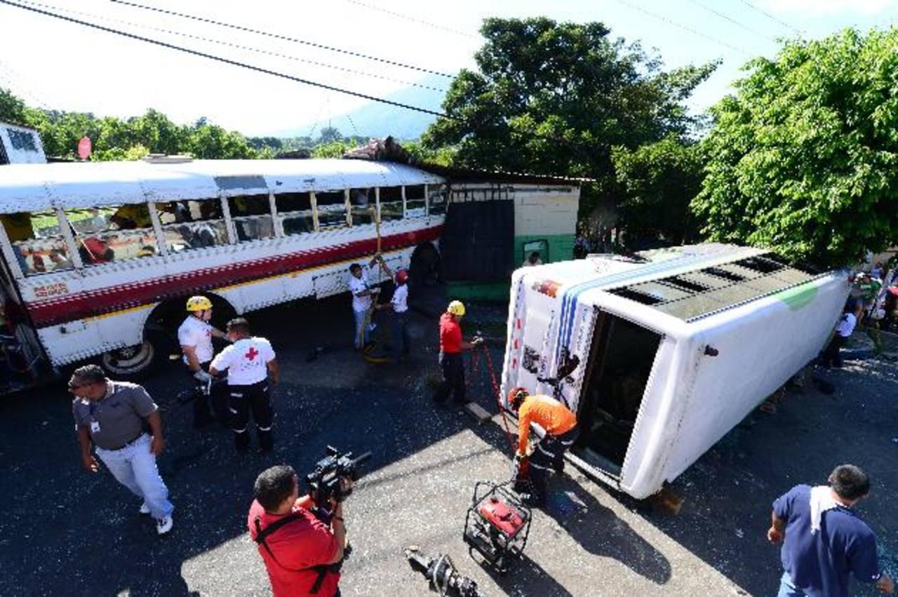 Este bus de la ruta 9 embistió al microbús que está volcado y luego se estrelló contra una pupusería. Foto EDH / Jorge Reyes.