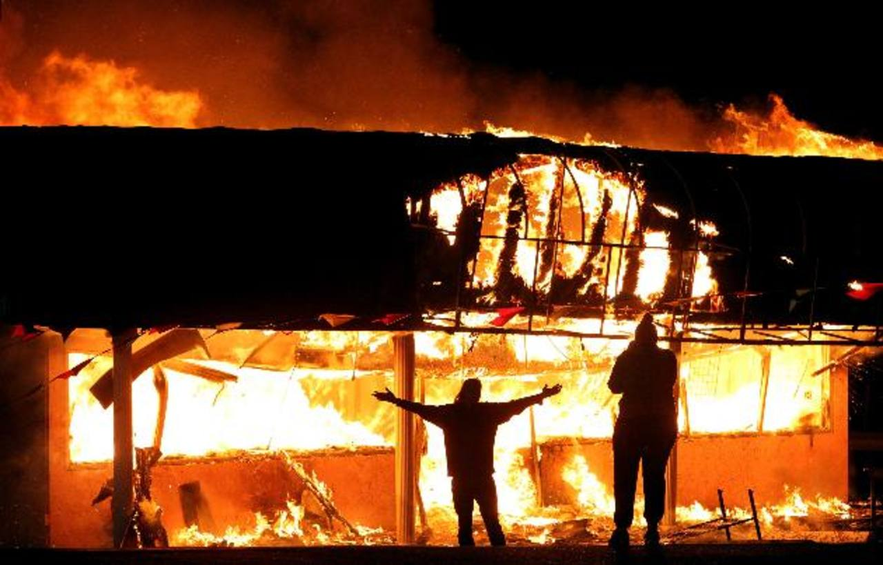 Manifestantes se fotografían frente a un negocio que fue incendiado en San Luis, Misuri, durante las protestas contra el veredicto que dejó libre a un policía blanco implicado en la muerte de un joven de color.