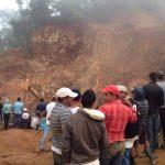 Familiares de víctimas y mineros artesanales observaban a dos maquinas excavadoras trabajar tras un derrumbe en la mina de oro.