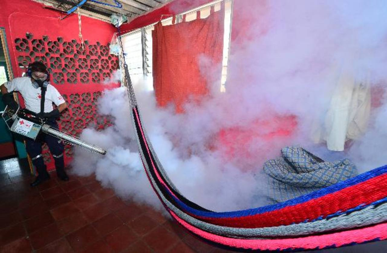 Un miembro de la Cruz Roja fumiga una vivienda en Ilopango. foto EDH / archivo.