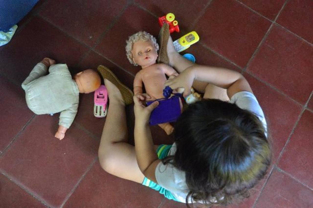 Johana, de tres años y medio, se entretiene con una cartera de juguete y una muñeca en su vivienda. Foto EDH / René Quintanilla