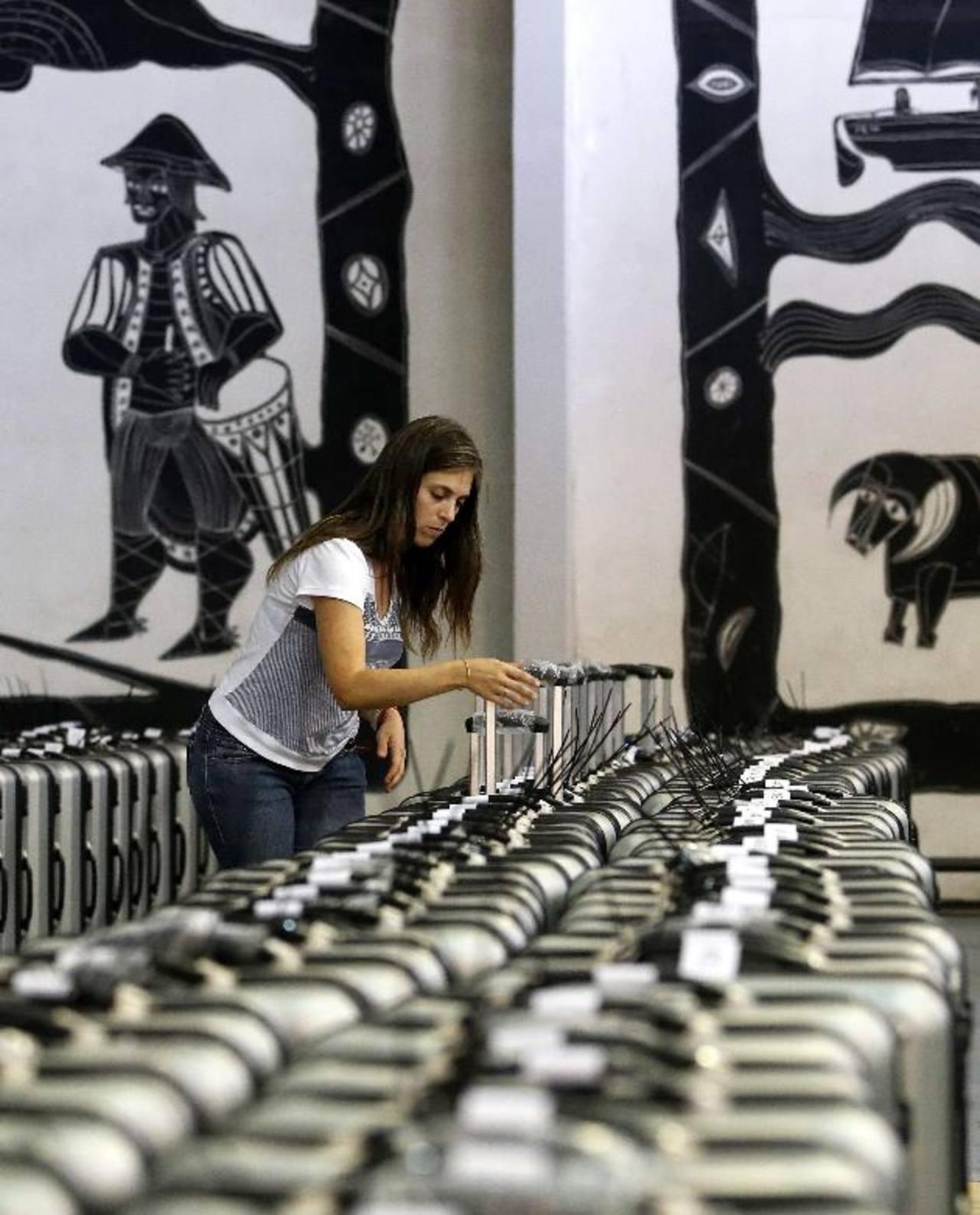 Una funcionaria electoral verifica las numeraciones de las urnas en un centro de votación en las afueras de Montevideo, para los comicios presidenciales de hoy. foto edh / Reuters.
