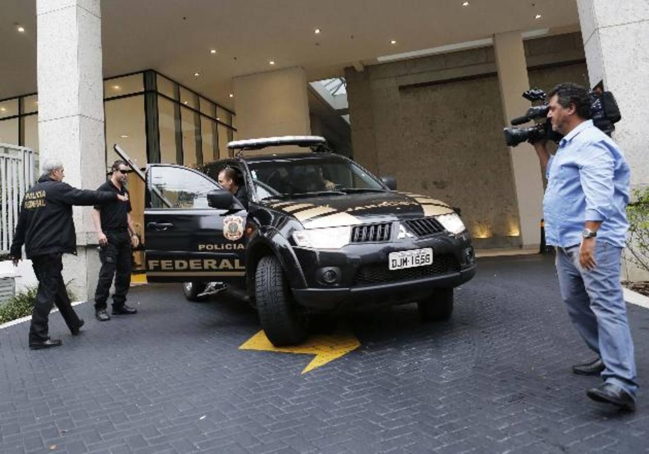 """Policías federales salen de la sede del conglomerado brasileño Camargo Correa, durante la operación conocida como """"Lava Jato"""" (lavado a chorro), ayer, en Sao Paulo, Brasil. foto edh / Reuters."""