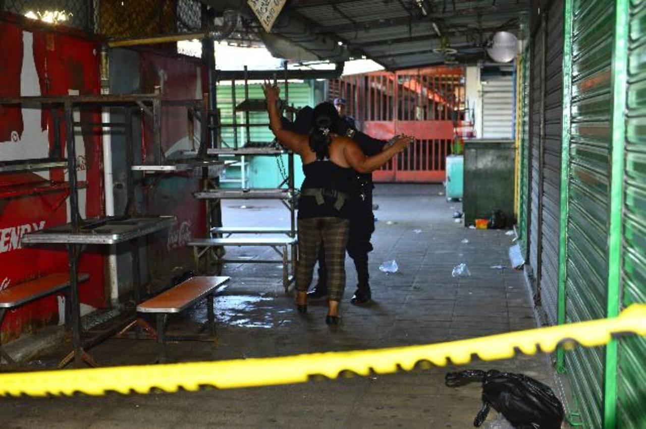 Un policía impide que una mujer se acerque al cadáver de uno de los hombres asesinados en el Mercado Central de San Salvador. Las autoridades presumen que las pandillas están tras el doble homicidio. Foto EDH / René Estrada.