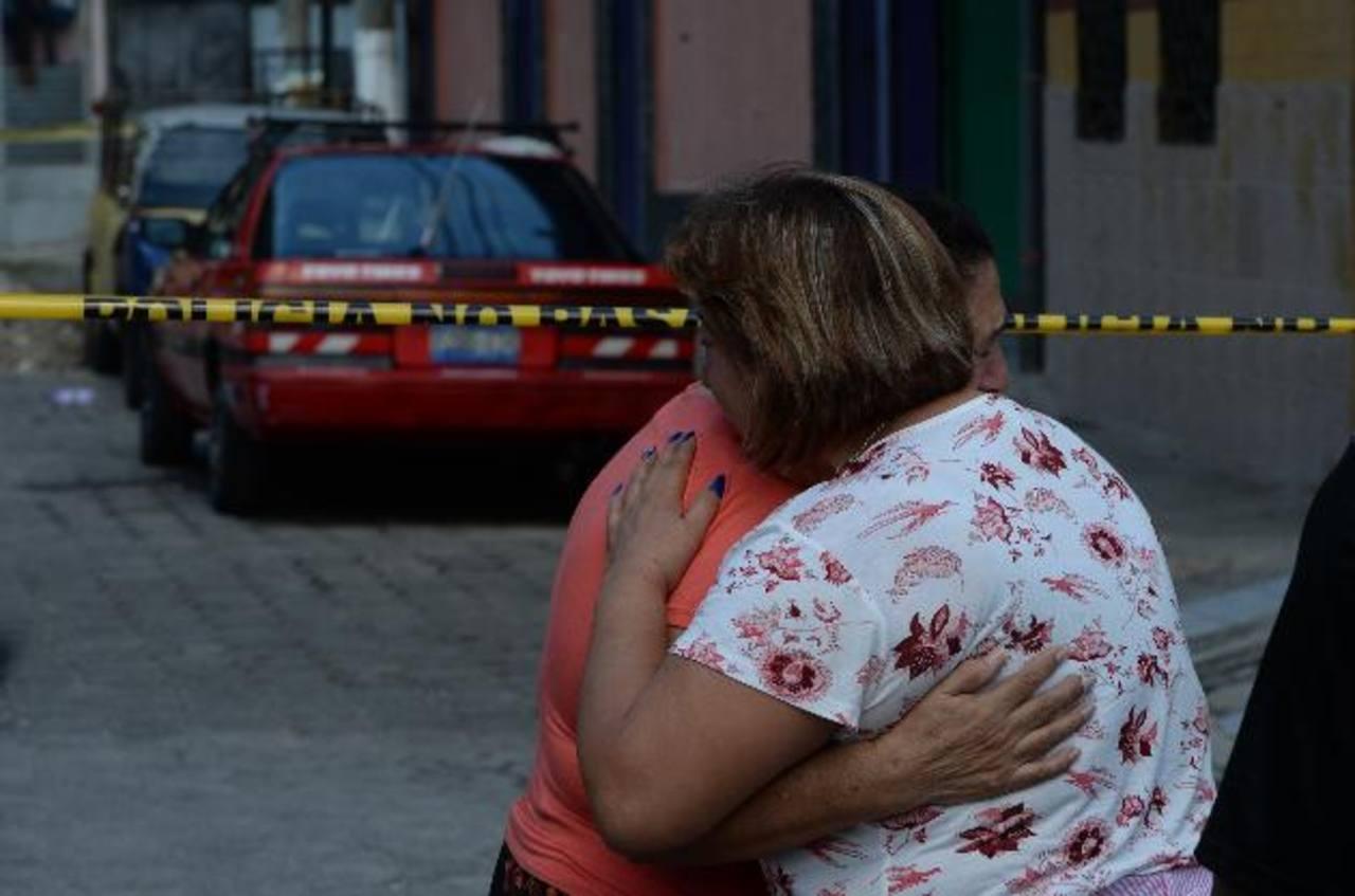 Parientes de Alejandro Adolfo Melara, de 26 años, se consuelan en la escena donde fue ultimado la víctima mientras lavaba su carro en la colonia San Juan. Foto EDH / Jaime Anaya.