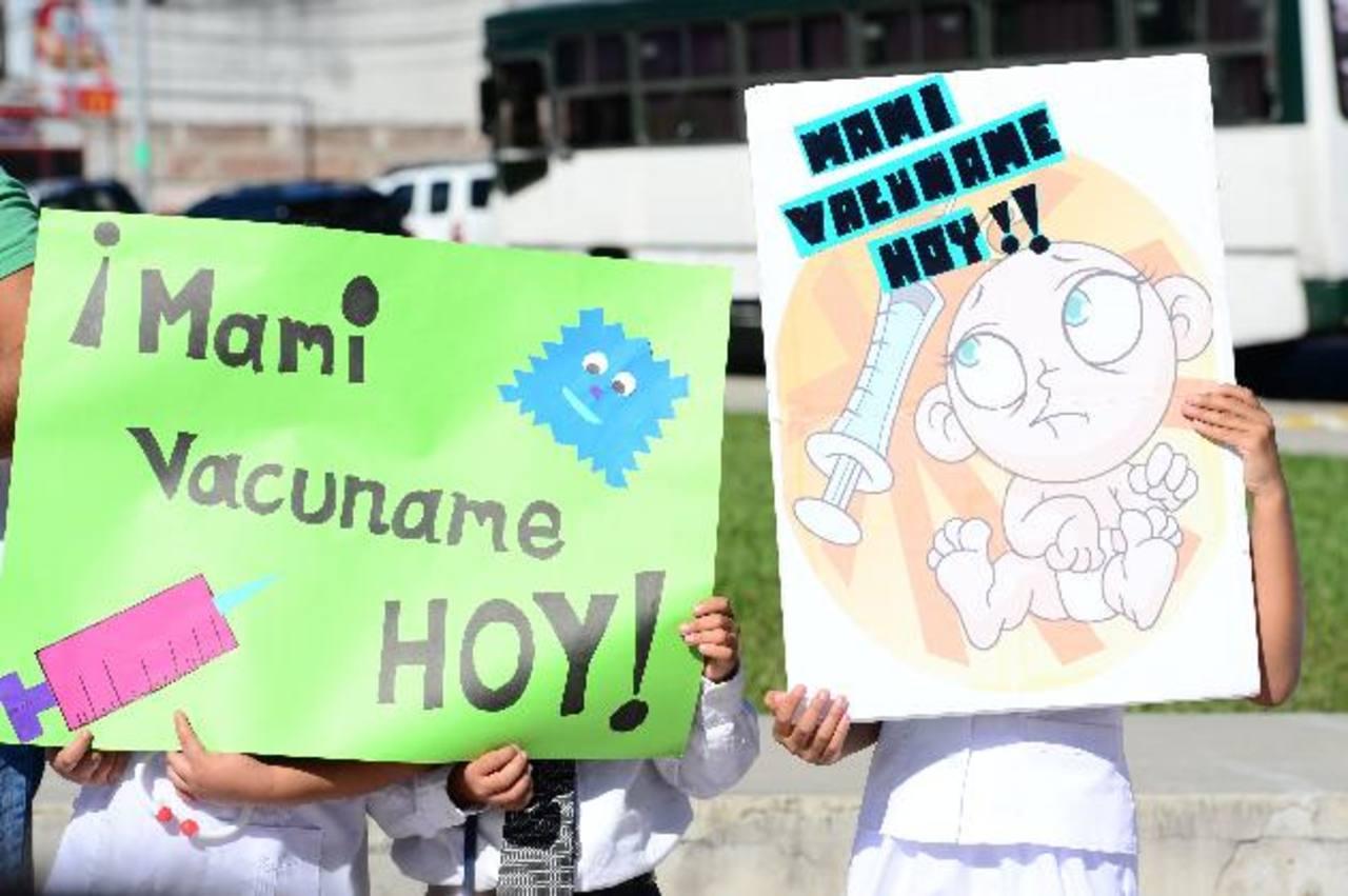 Niños portan carteles con mensajes que incentivan a ponerse las vacunas. Foto EDH /Jorge Reyes