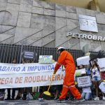"""Un manifestante limpia la entrada del edificio central de Petrobras en una protesta para exigir """"limpieza"""" en la compañía estatal petrolera."""