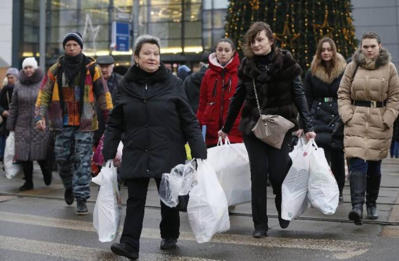 Varios moscovitas cruzan una calle cargados de bolsas en medio del frenesí de los consumidores por comprar productos antes de que los precios se disparen.