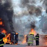 Bomberos tratan de apagar los automóviles que fueron incendiados durante las protestas de ayer. foto edh / ap
