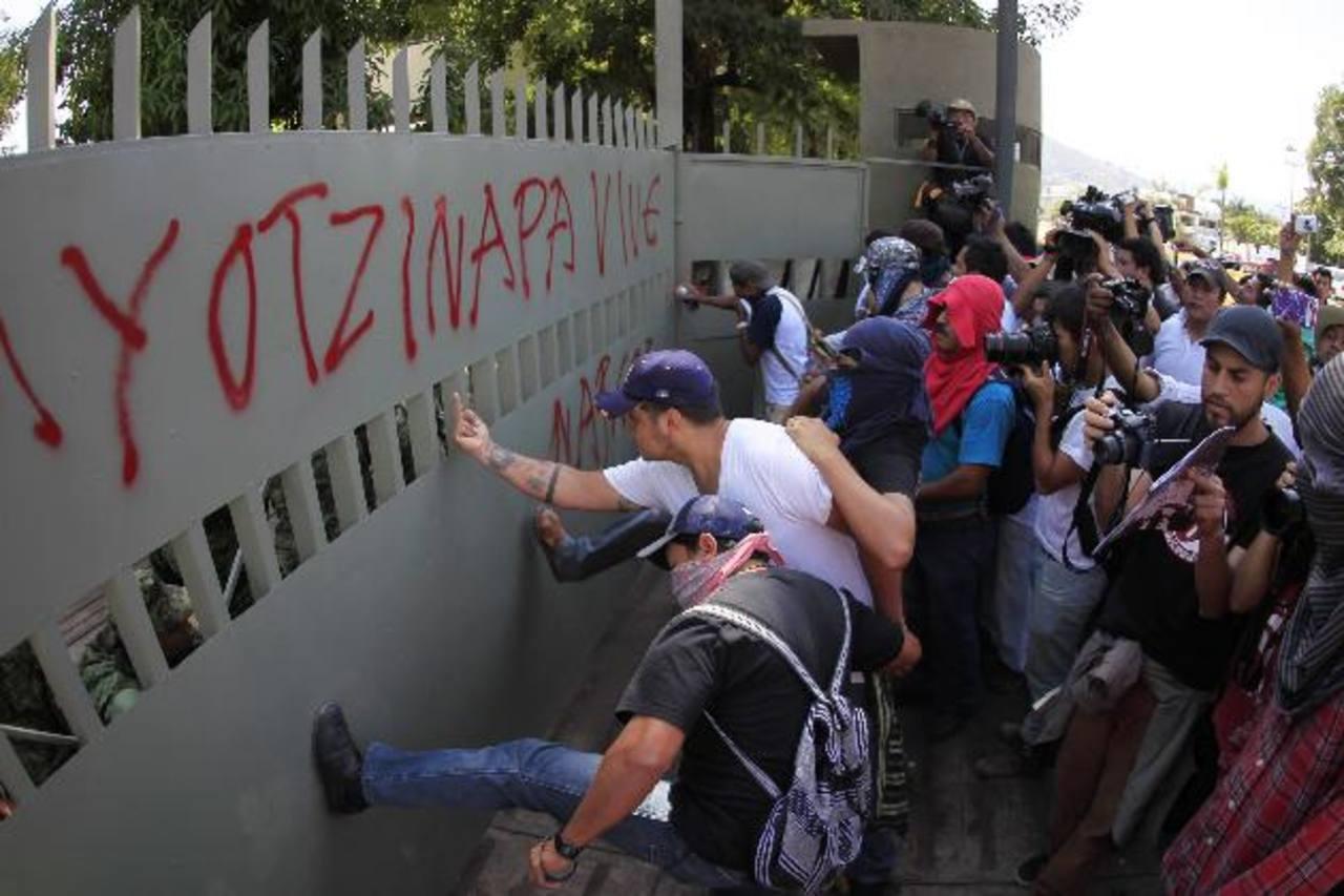 Los manifestantes lanzan patadas a la puerta del batallón de infantería durante la protesta de ayer en Iguala. foto edh / Reuters