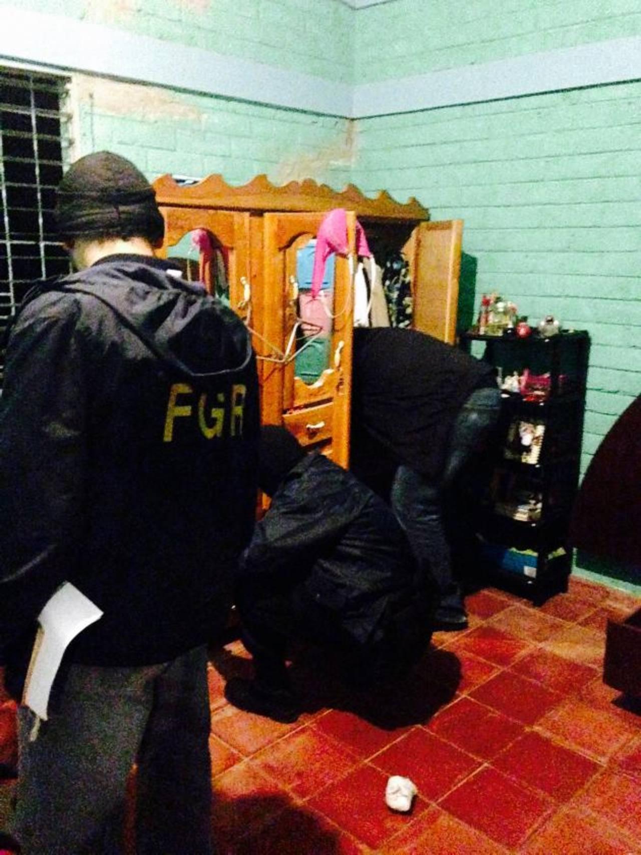 Fiscales y policías registran la casa de un supuesto pandillero detenido en La Libertad. Foto EDH /