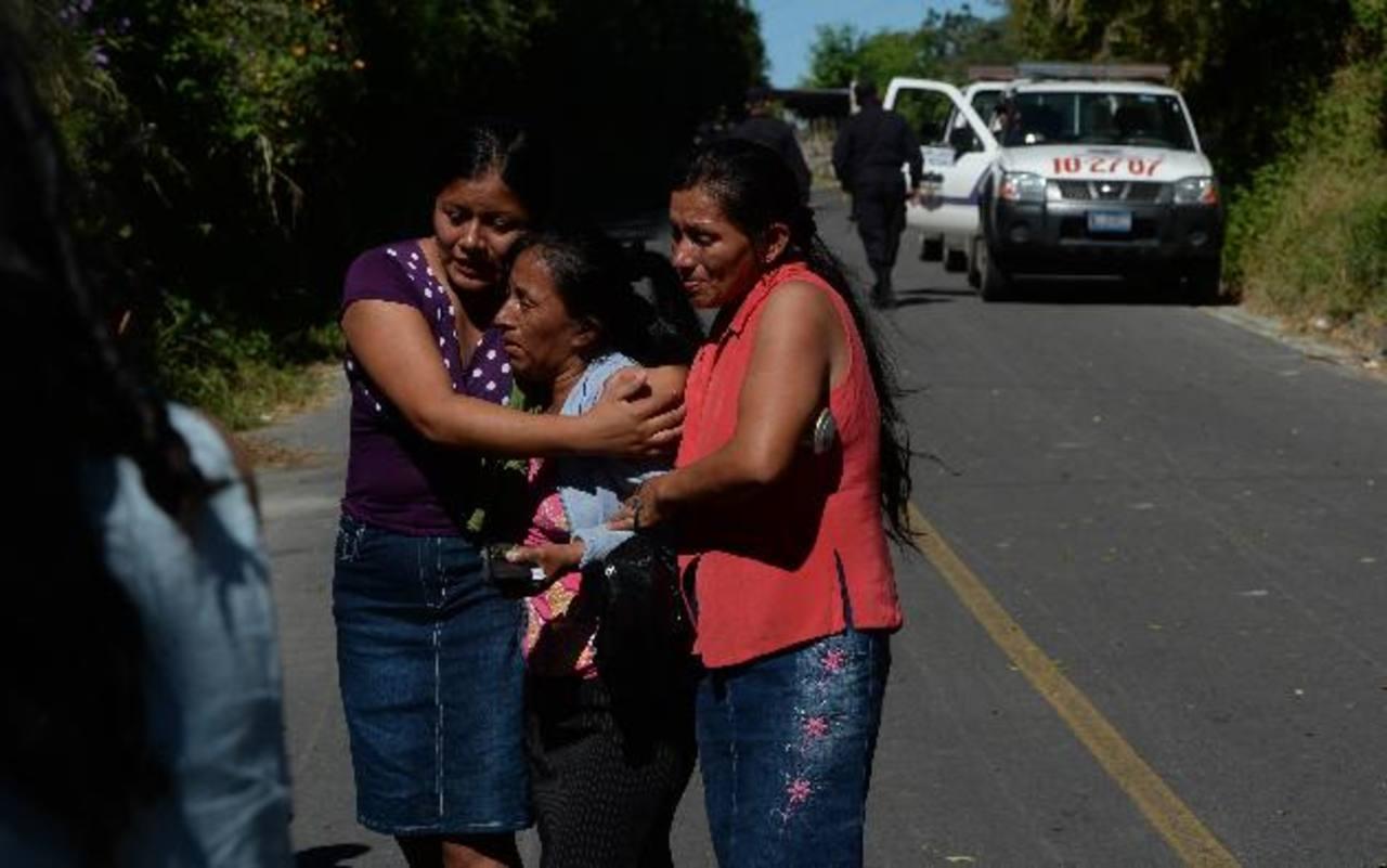 Dos mujeres consuelan a la madre de Armando Bonifacio Guzmán, panadero asesinado ayer en El Carmen, Cuscatlán.