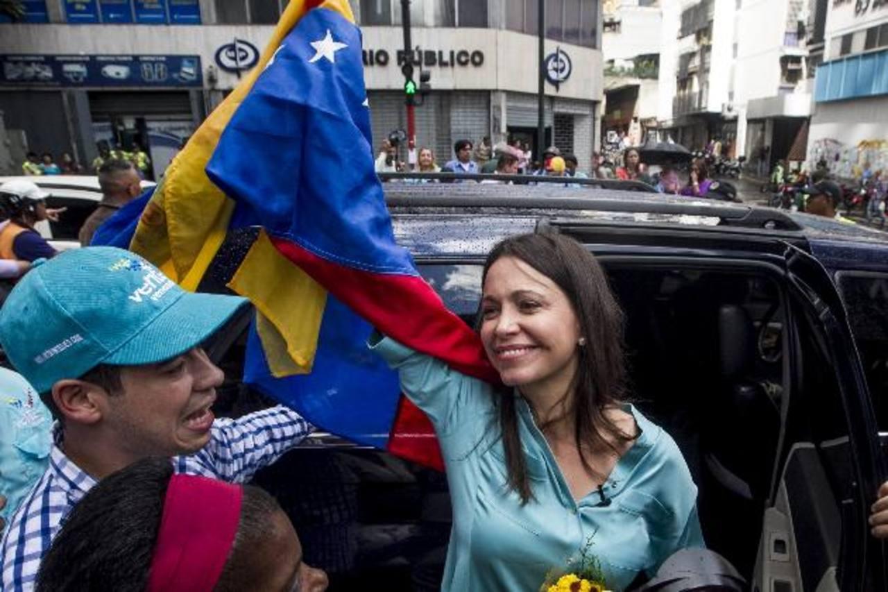 María Corina Machado saluda a seguidores en las inmediaciones al Ministerio Público luego de retirarse del recinto. foto edh /EFE