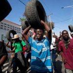Manifestantes antigubernamentales llevan neumáticos para quemarlos en barricadas con las que cerrarán calles en Puerto Príncipe, Haití.
