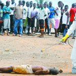 Un trabajador de salud rocía con químico a una persona sospechosa de tener ébola. foto edh / AP.