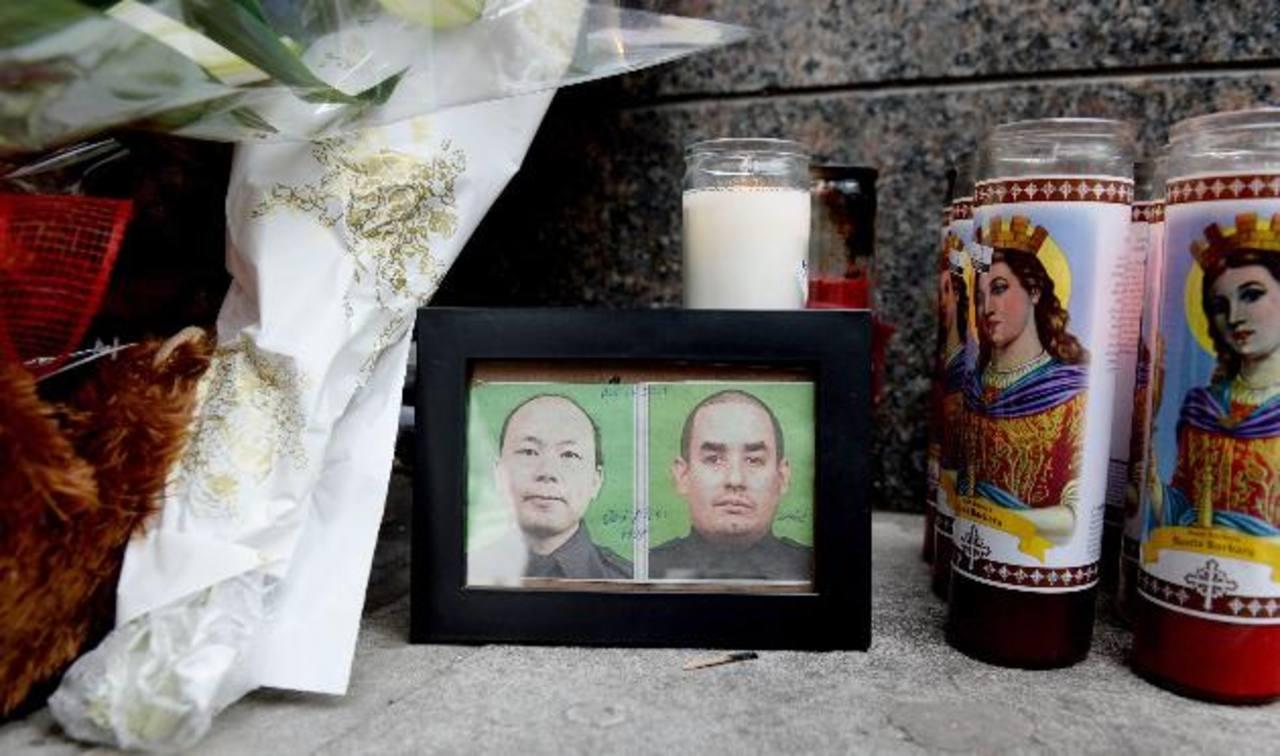 La fotos de los agentes asesinados Wenjian Liu (i) y Rafael Ramos (d), fuera del Precinto 84 de la policía, en Brooklyn, Nueva York.