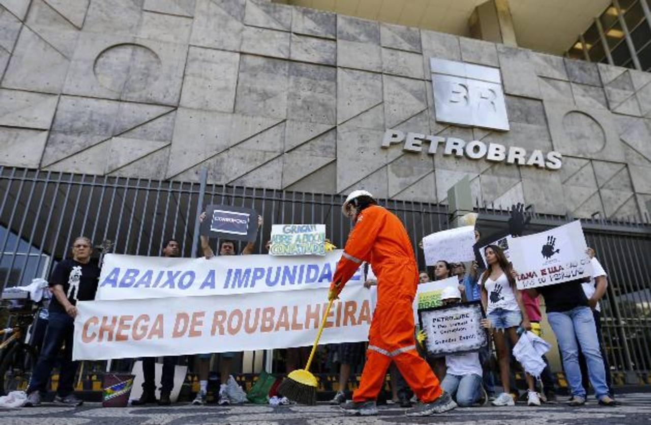 Un manifestante limpia la entrada principal de la sede de Petrobras en Río de Janeiro, durante una protesta contra la corrupción y contra el gobierno de Rousseff. foto edh / Ruters