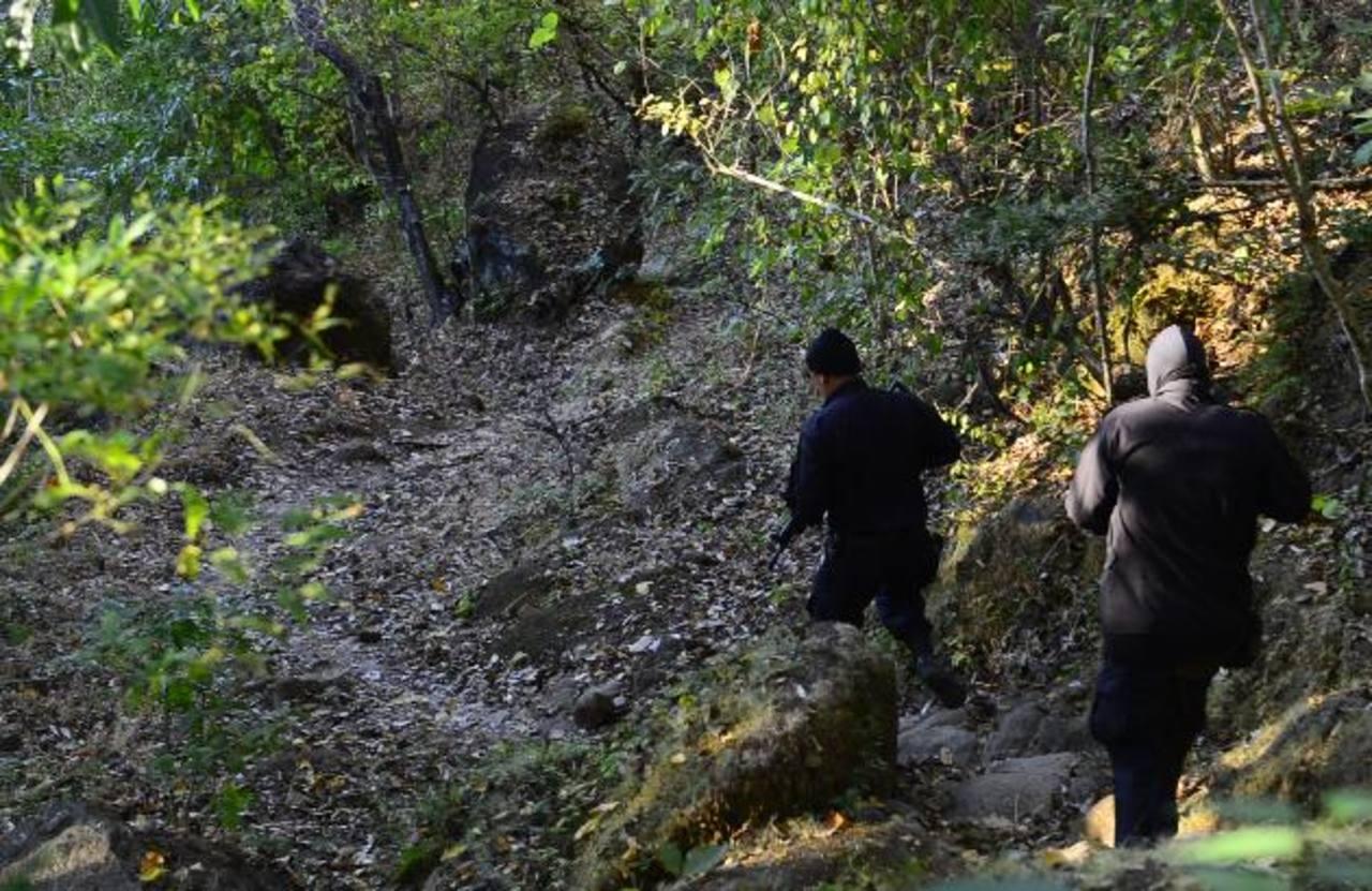 Agentes bajan a la zona donde la tarde del miércoles pasado asesinaron a cinco personas que se bañaban en un poza en las afueras de San Lorenzo, Ahuachapán. Foto EDH / Archivo