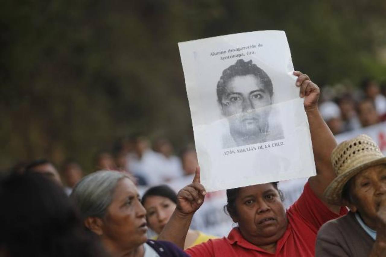 Una mujer sostiene una foto de uno de los estudiantes desaparecidos.