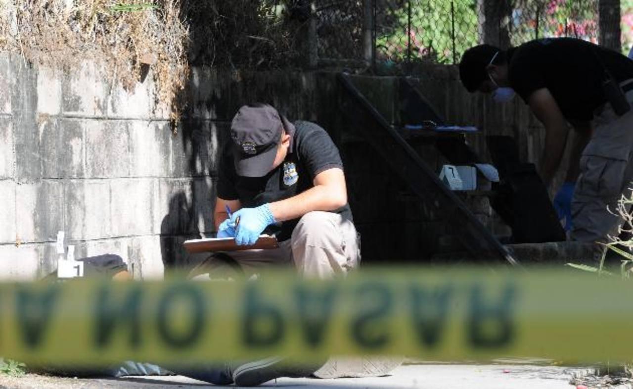 Policías recogen evidencias en el lugar donde ayer en la madrugada fue acribillado un joven que estudiaba segundo año de Medicina en la Universidad de El Salvador. Foto EDH / CLAUDIA CASTILLO.
