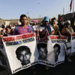 Manifestantes sostienen fotografías de los 43 estudiantes durante una protesta en Ciudad de México. foto edh /archivo