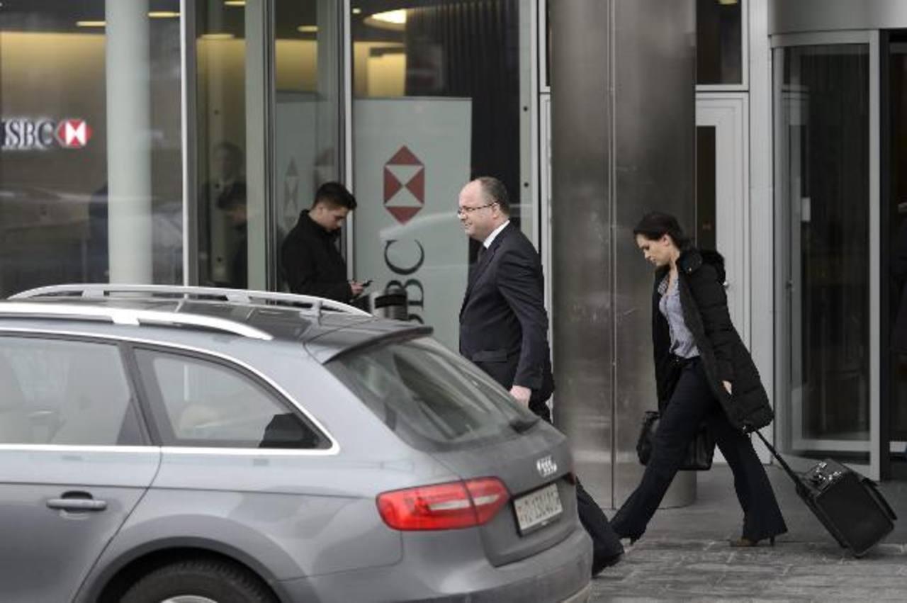 Oliver Hornot (centro), fiscal del cantón de Ginebra, sale de las oficinas de la filial suiza del banco HSBC en Ginebra hoy, miércoles 18 de febrero.