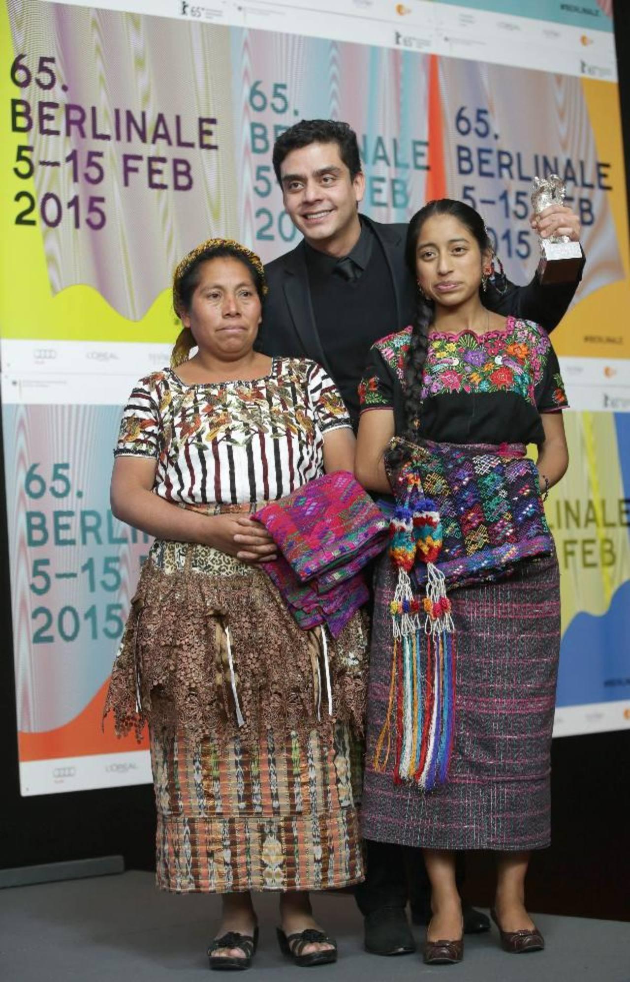 El director guatemalteco, en medio de las actrices María Telón (izq.) y María Mercedes Coroy (der.), con el Oso de Plata. FOTO EDH / EFE