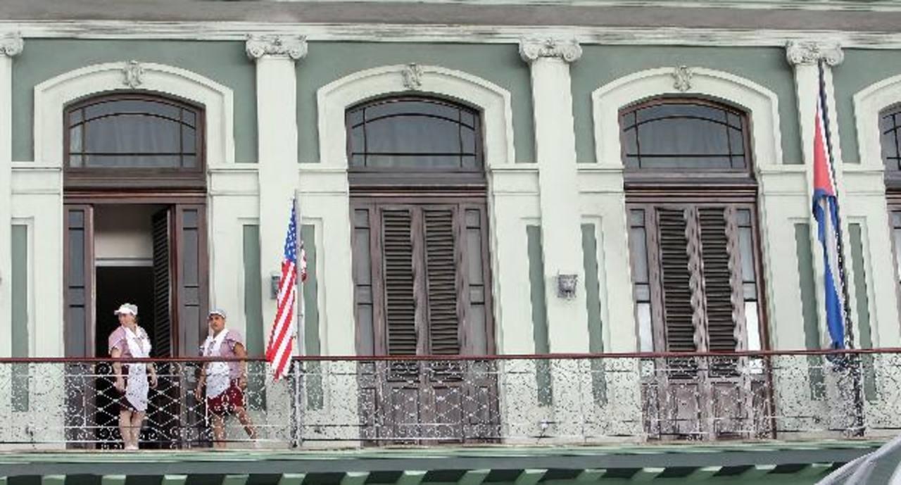 Dos empleadas acomodan una bandera estadounidense en el hotel donde llegó una comitiva de senadores de EE. UU. foto edh / efe
