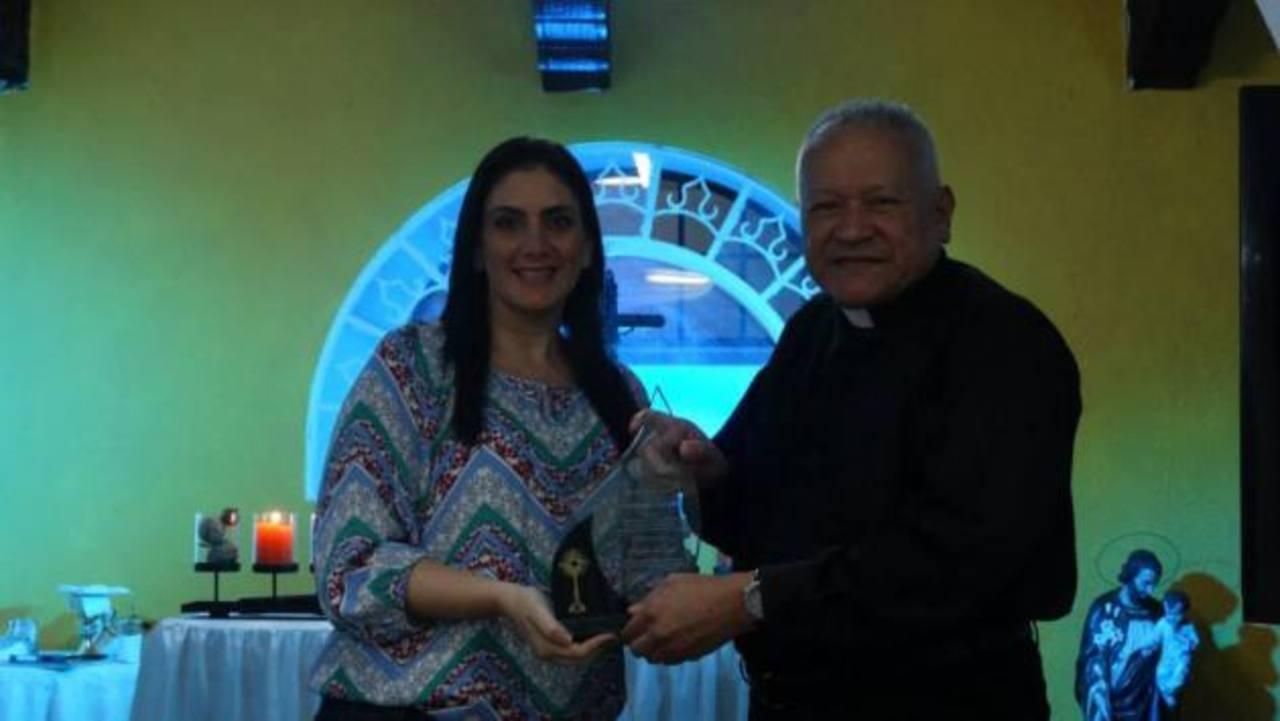 Brenda de Miguel, de Fundación TCS, recibió uno de los reconocimientos del manos del padre Martín Ávalos.