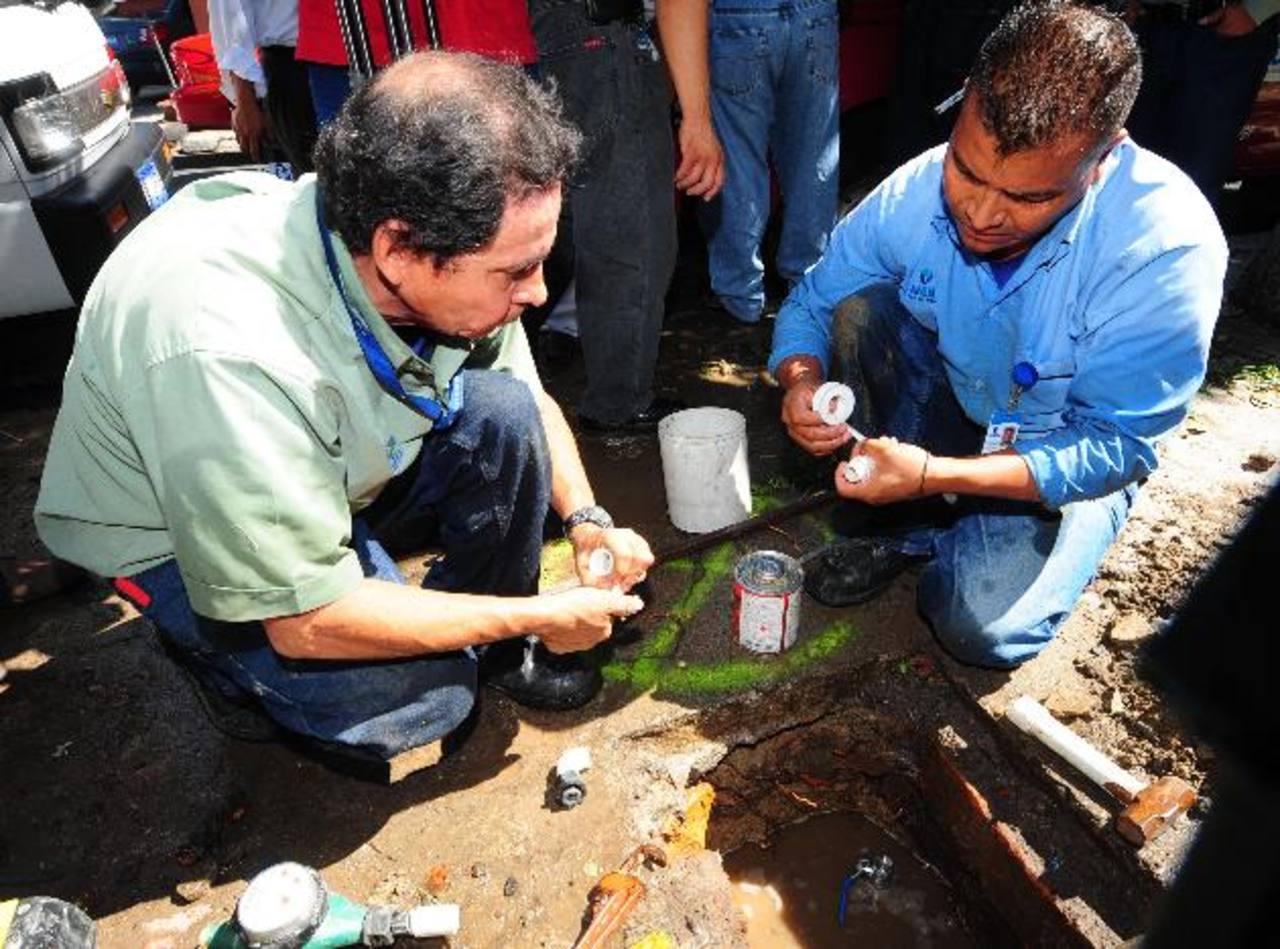 Fontaneros contratados por la Anda realizan un cambio de contador. Foto EDH / Archivo