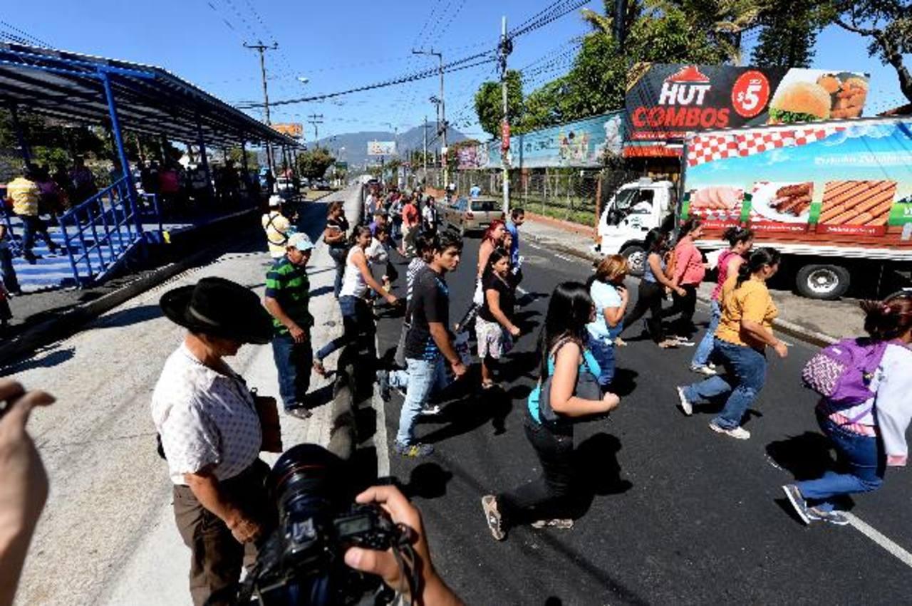Usuarios cruzan a toda prisa desde los carriles centrales del Sitramss hacia las aceras o viceversa.