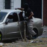 Un agente recoge evidencias donde murieron ayer dos vigilantes en residencial Montebello, en San Salvador, al tratar de impedir el robo de un vehículo. Foto EDH / Jaime Anaya.