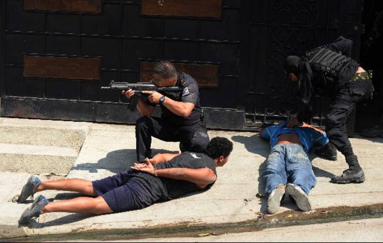Policías custodian a dos de los pandilleros detenidos ayer en Mejicanos. Foto EDH / Marlon Hernández
