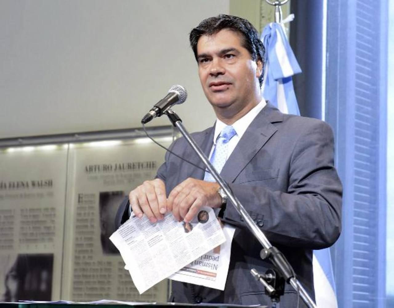 El jefe del Gabinete argentino, Jorge Capitanich, hace trizas dos páginas del diario Clarín. foto edh / efe