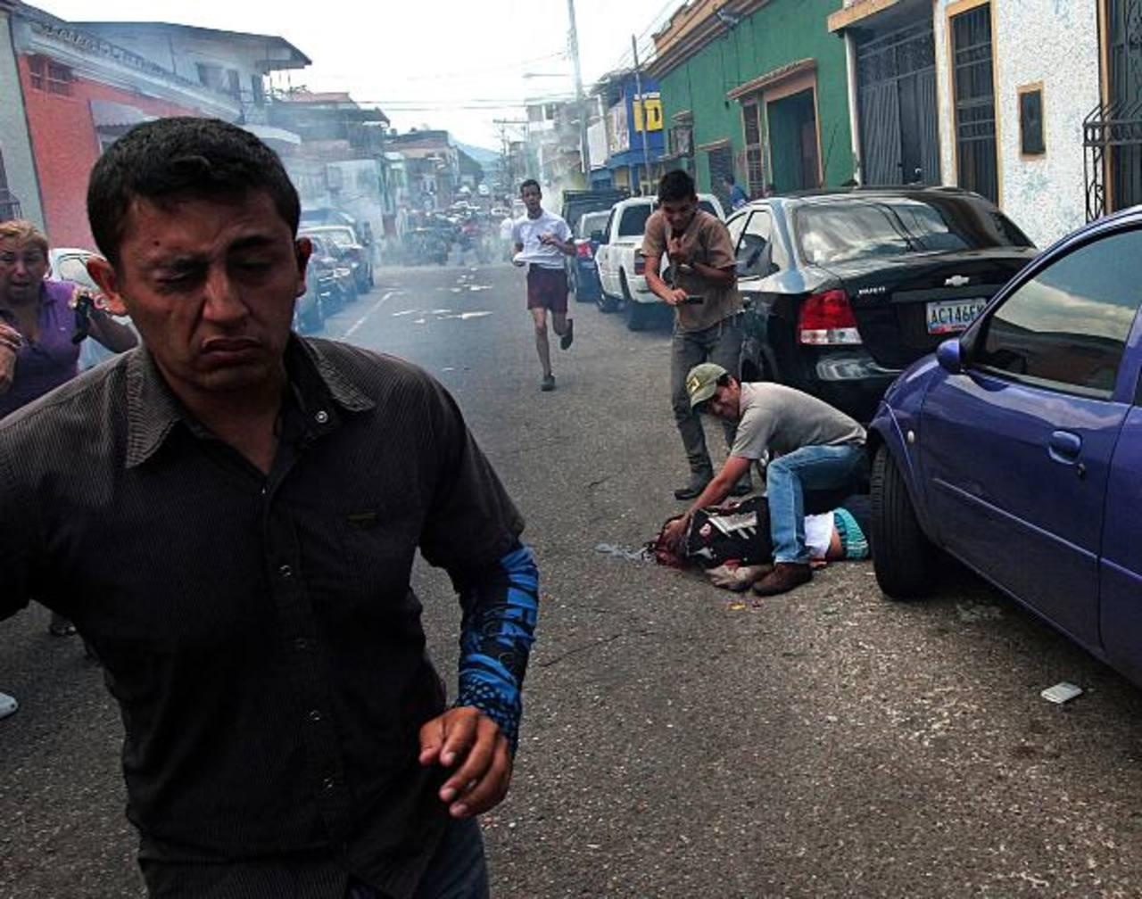 Al fondo, un hombre trata de auxiliar al joven estudiante que recibió el disparo en la cara.