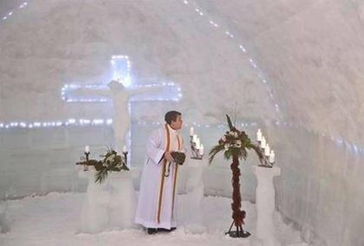 Un sacerdote apaga velas en una iglesia hecha totalmente de bloques de hielo.