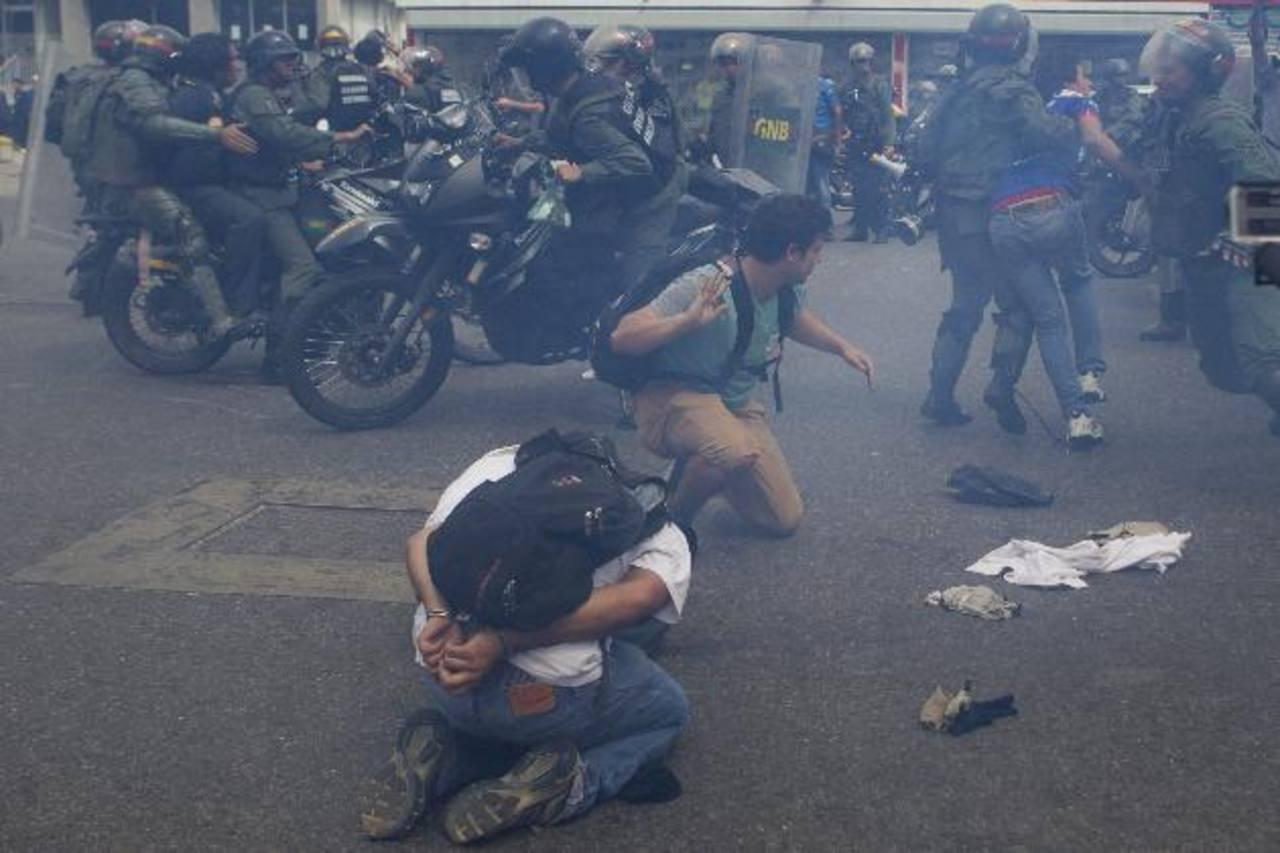 Manifestantes son detenidos por miembros de la Guardia Nacional Bolivariana (GNB).