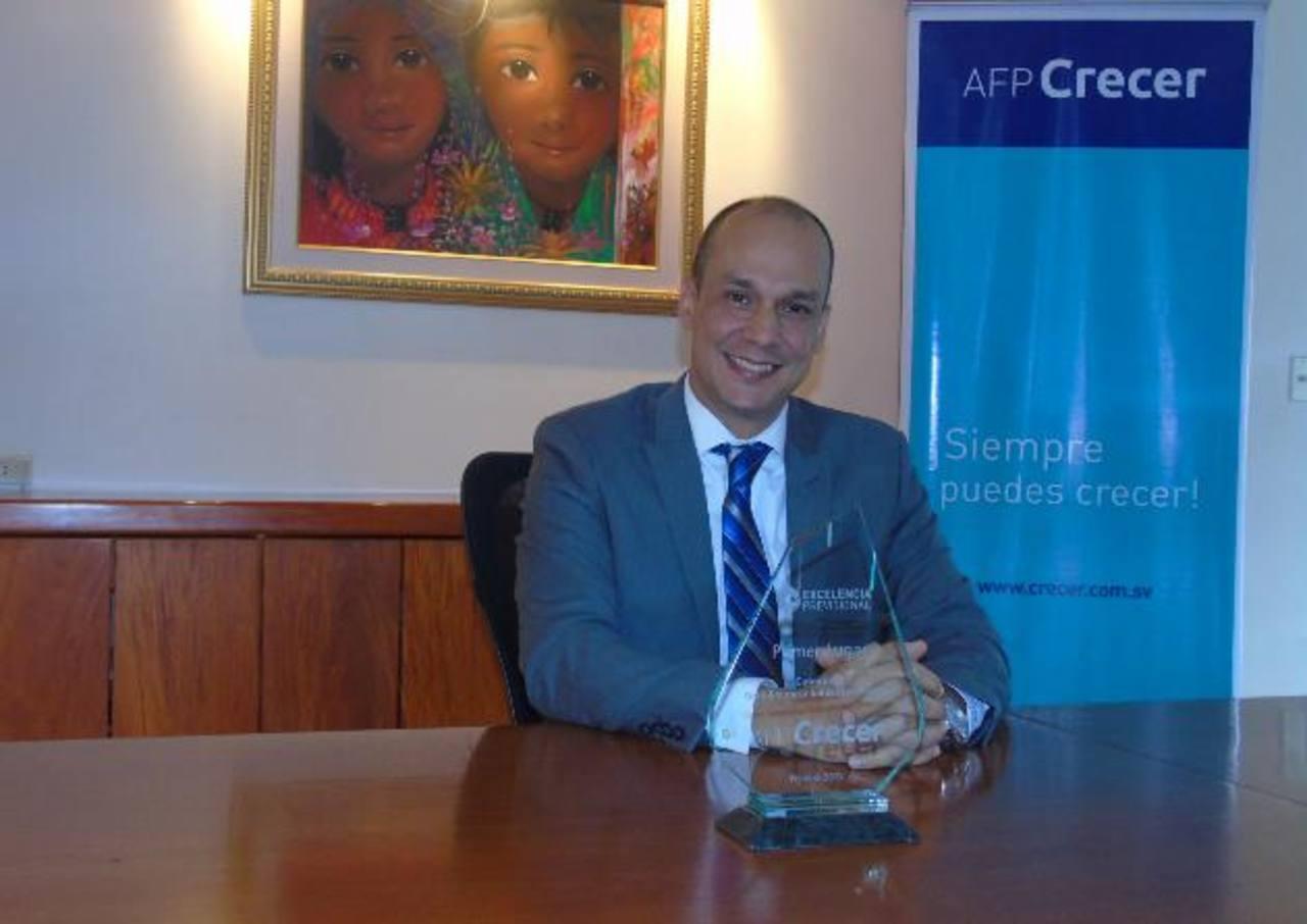 Augusto Morales, director Comercial y de Mercadeo de AFP Crecer, con uno de los premios. Foto EDH / Cortesía AFP Crecer.