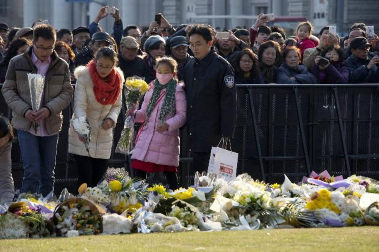Varias personas han colocado arreglos florales en honor a las víctimas de la estampida registrada en Año Nuevo en Shanghái.