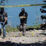 Las víctimas fueron sacadas de su casa, ubicada a orillas del lago Suchitlán, para ser asesinadas a tiros por unos siete delincuentes. Policías recogen evidencias.