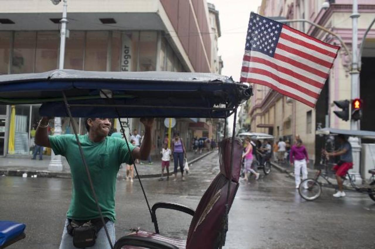 Un joven acomoda la capota de su bicitaxi, vehículo usado como medio de transporte. Foto EDH