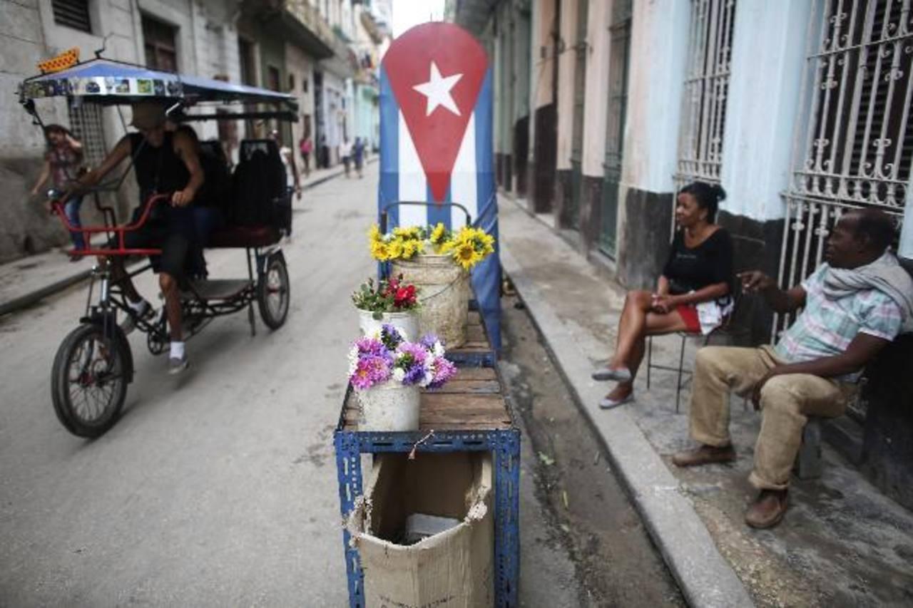 Para poder sobrevivir, Pedro Paterson, de 50 años, (der) vende flores a los transeúntes de las calles de La Habana. foto edh / archivo