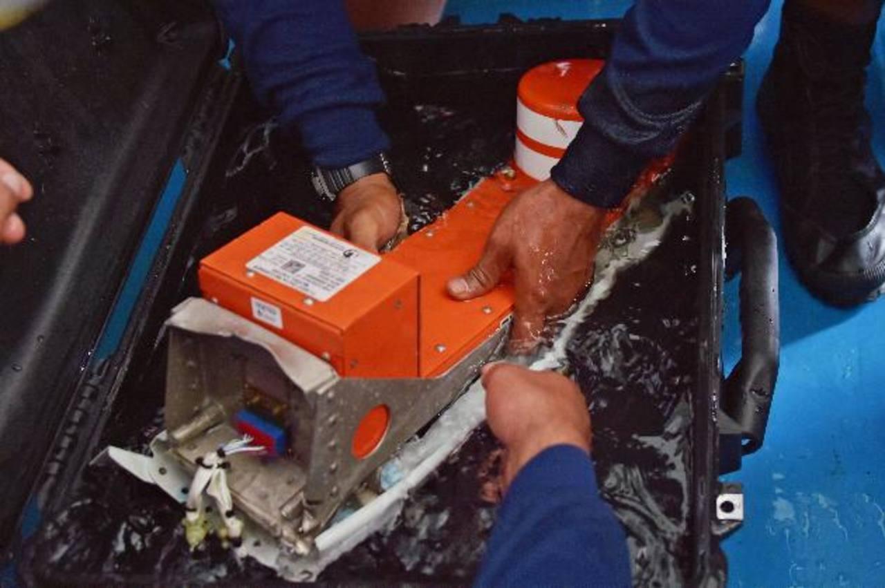 Buzos de la marina manipulan la caja negra del avión de AirAsia accidentado en diciembre.