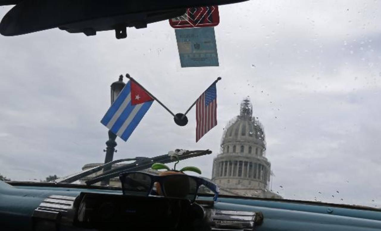 Banderas de Cuba y EE. UU. decoran el interior de un taxi que pasa frente al edificio del Capitolio en La Habana. foto edh /AP