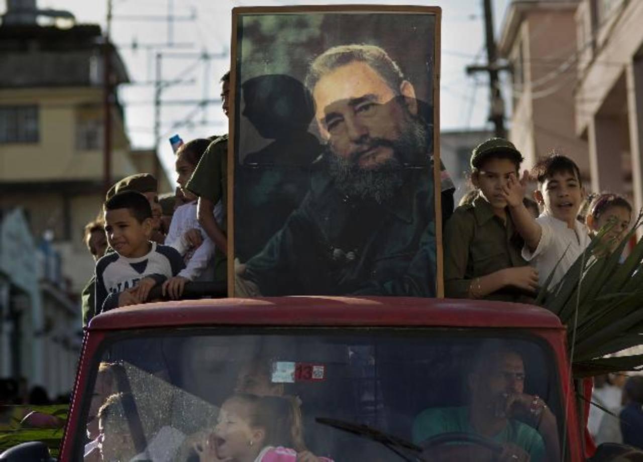 """Un grupo de niños lleva una fotografía de Fidel Castro durante una caravana ayer, en La Habana, en el marco del 56 aniversario de la """"Caravana de la Libertad"""" en 1959. foto edh / AP."""
