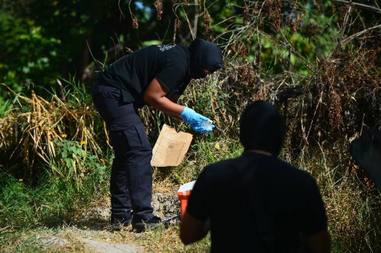 Policías buscan evidencias en el sitio donde hallaron el cadáver de un hombre en 50a. Avenida Norte. Fotos EDH / RENÉ QUINTANILLA