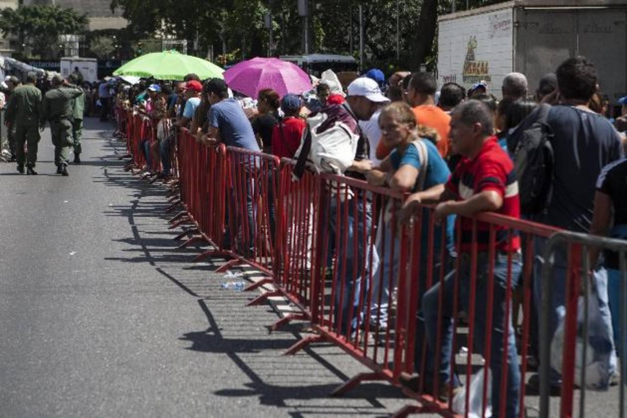 Decenas de venezolanos hacían fila ayer para ingresar a un mercado improvisado y comprar comida regulada por el gobierno chavista en Caracas, mientras otros protestaban por la escasez. EFE