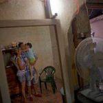 Un día después de su liberación, Wilberto Parada, de 42 años (al centro), con su hijo y esposa, son vistos reflejados en un espejo durante una entrevista en su casa en La Habana, Cuba.