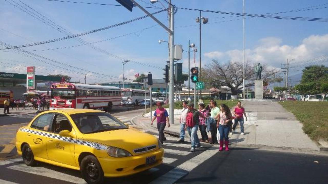 Sobre la 38 avenida Norte, los peatones intentan cruzar pero un taxi les corta el paso. Foto / Lilian Martínez.